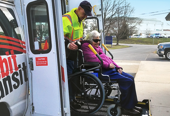 accessibility image featuring a woman in wheelchair being assisted on a lift