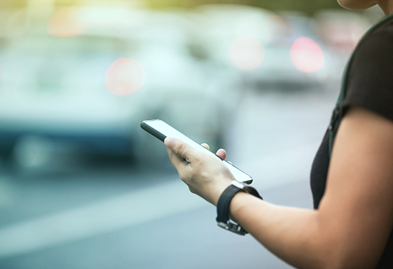 Woman hands using smartphone at city street side,checking the ride-hailing apps