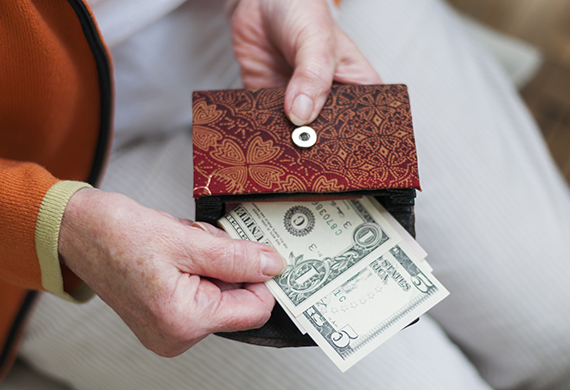 senior woman pulling cash from her purse