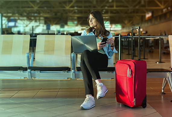 Passenger on smart phone and laptop sitting in airport terminal hall