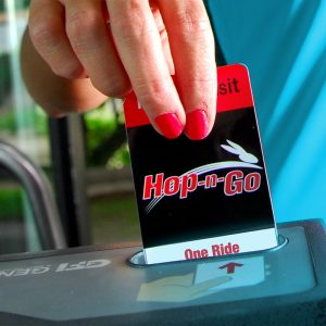 image of a hand inserting a Hop-N-Go pass into the farebox