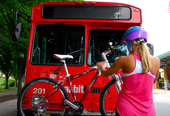 Woman in a bike helmet strapping a bike to the front of a rabbitransit bus