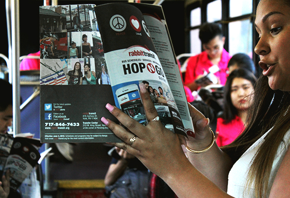woman holding a Hop N. Go guide with riders in the background on bus