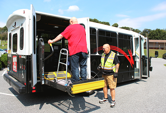 rider entering a paratransit vehicle with an assisted lift